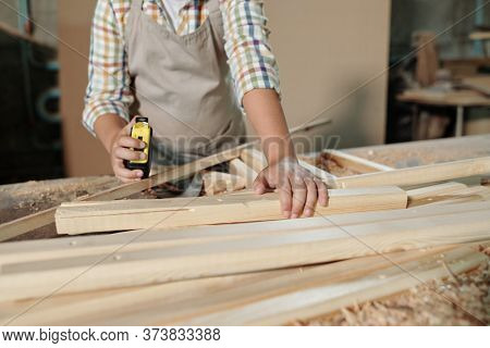 Close-up of unrecognizable boy in apron using tape measure while working with wooden details in joinery workshop