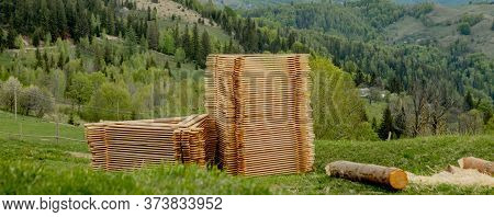 Piles Of Wooden Boards On Green Grass With Mountains On Background, Planking For Construction. Wood