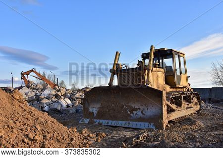 Bulldozer At Landfill For Work Concrete Demolition Waste. Salvaging And Recycling Construction Mater
