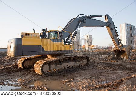 Excavator Working At Construction Site On Earthworks. Backhoe On Road Work Digs Ground. Paving Out S