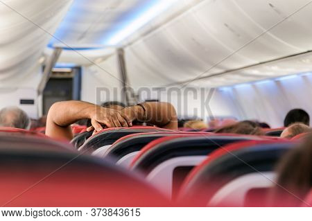 The Arms And Hands Of A Passenger Looking A Movie Or Resting In The Economy Cabin Class Of An Airpla