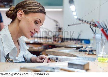 Jeweler working with tools on a piece of jewelry at her workbench