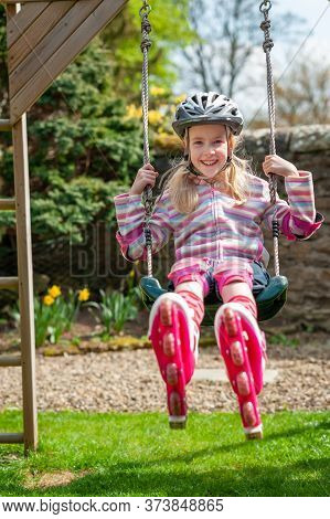 A Smiling Young Blonde Girl Wearing Roller Blades And Helmet While Swinging On A Garden Swing.