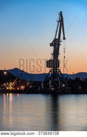 A Shipping Crane In The Port Of Petropavlovsk, Russia At Sunset.