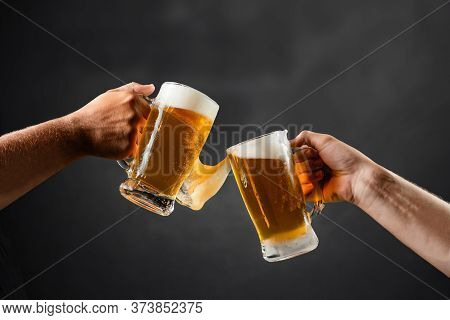 Two Hands With Beer Mugs, Toasting In Celebration, With Overflowing Foam, Dark Background And Space