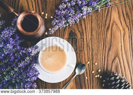 Cup Of Coffee With Foam Made In A Coffee Pot Decorated  With Lavender Flowers, Cedar Nuts And Cown O
