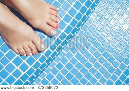 Colorful Stylish Summer Pedicure Foot On A Blue Waterpool Background.
