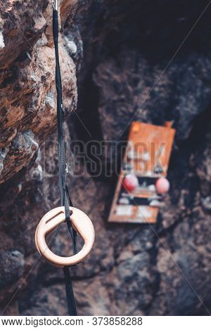 Wooden Sport Rings Hanging On A Rock For Outdoor Climb Training Practice.