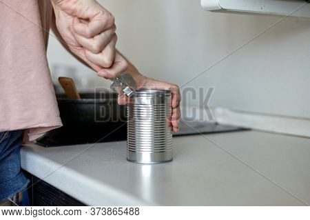 A woman in the kitchen opens a can. Hand open canned food in metal can. Close up canned goods non pe