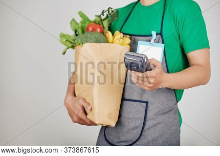 Cropped Image Of Supermarket Worker Carrying Package Of Fresh Groceries And Payment Terminal