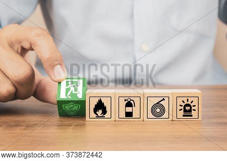 Close-up Hand Choose A Wooden Toy Blocks Stacked With Fire Exit Icon For Fire Safety Protection Conc