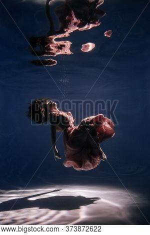 Woman Wear Fashionable Pink Dress Sea Underwater. Attractive Young Lady Model With Long Brunette Hai