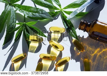 Gelatin Softgels Capsules Of Omega 3 Fats Decorated With Green Leaves On White Background. Fish Oil.