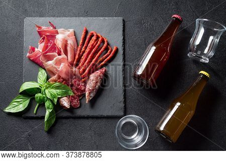 Prosciutto, Sausage Fuet And Chorizo, Bottled Beer On A Black Slate Board. Antipasti Concept.