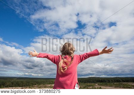 Carefree Girl Child With Hands Up Against Sky Clouds Outdoors