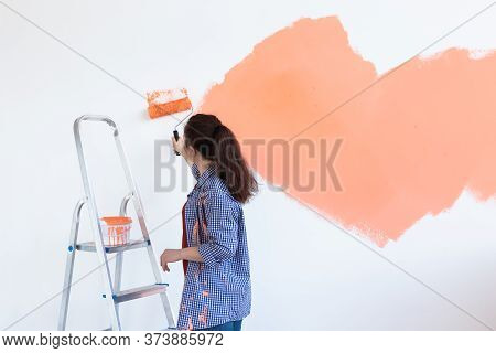 Happy Young Woman Painting Wall In Her New Apartment. Renovation, Redecoration And Repair Concept. C