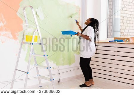 Young Happy African American Woman Painting Interior Wall With Paint Roller In New House. A Woman Wi
