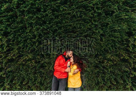 A Couple In Love Is Lying On The Green Grass. A Beautiful Couple In Red And Yellow Jackets Embrace.