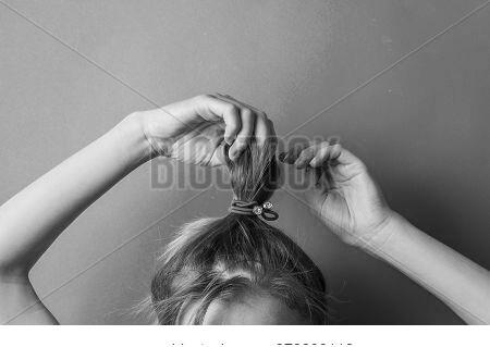 Girl Straightens The Disheveled Tail Of Hair On Her Head, Against A Blue Background. Modern Fast Hai