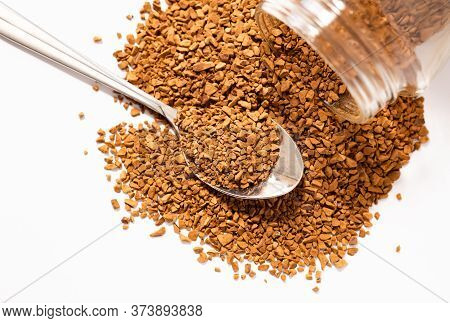 Instant Coffee Sprinkled From A Can, A Full Spoon Of Granulated Coffee Close-up, Isolate On A White