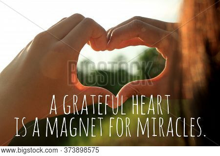 Inspirational Quote  - A Grateful Heart Is A Magnet For Miracles. With Young Woman Hands Making Love