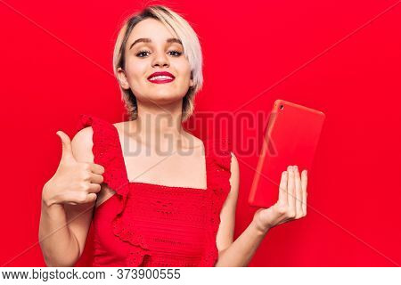 Young beautiful blonde woman holding touchpad smiling happy and positive, thumb up doing excellent and approval sign
