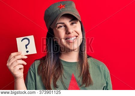 Beautiful woman wearing cap with red star communist symbol holding question mark reminder looking positive and happy standing and smiling with a confident smile showing teeth