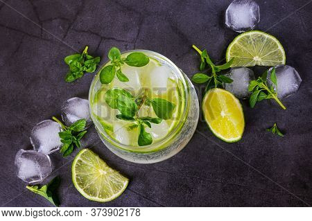 Lime Mojito In Transparent Glass On Dark Background. Around - Pieces Of Fresh Lime, Ice And Mint. To