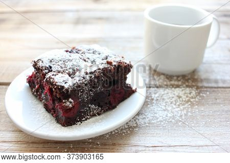 Cup Of Coffee With Handmade Chocolate Cake On Wooden Table Background. Brownie With Cherries On A Wh