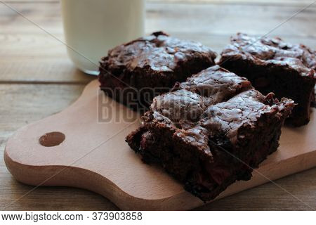 Brownies With Cherries On A Cut Board. Close-up Of Handmade Chocolate Cake And A Glass Of Milk On Wo