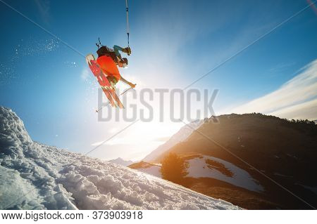 Man Skier In Flight After Jumping From A Kicker In The Spring Against The Backdrop Of Mountains And
