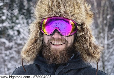 Close-up Portrait Of A Bearded Happy Snowboarder Skier In A Ski Mask With Goggles And A Fur Big Old-