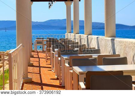 Beautiful Picturesque Summer View Of A Cafe With White Columns By The Sea. Brown Tables Against The