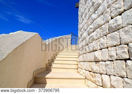 An Old White Stone Staircase Leads Up To The Tower Of A Medieval Fortress. The Element Of Architectu