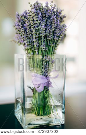 A Bouquet Of Lavender With Ribbons In A Beautiful Glass Vase On The Table