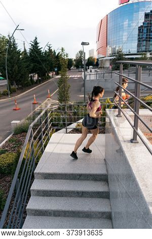 Young Woman Running On Staircase In Morning. Health Conscious Concept. Healthy Active Lifestyle. Act