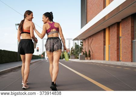 Young Woman Jogging On Sidewalk In Morning Talking. Health Conscious Concept. Healthy Active Lifesty