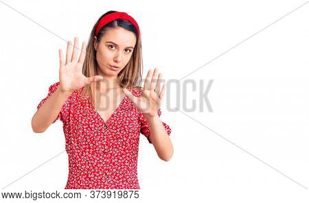 Young beautiful girl wearing dress and diadem moving away hands palms showing refusal and denial with afraid and disgusting expression. stop and forbidden.
