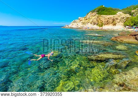 Female Bikini Snorkeling In Cotoncello Beach Near Popular Sant Andrea Beach In Elba Island. Snorkele