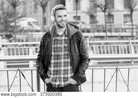 Street Beats. Happy Guy Wear Headphones Urban Outdoor. Handsome Man Listen To Music Playing In Stere