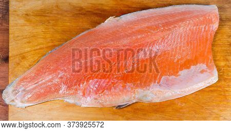 Trout Fillet On The Skin As A Boneless Half Of The Fish Lies Skin Side Down On The Old Wooden Cuttin