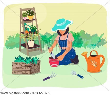 Gardener Plants Flowers In The Garden.an Agricultural Worker Plants Seedlings.the Girl Is Fond Of Ga
