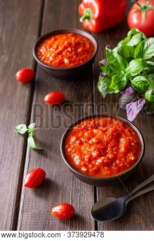 Balkan Sauce Ajvar In A Clay Bowl And Ingredients For Its Preparation On A Wooden Background. Serbia