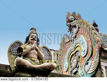 A Sculpture Of A Mythological Creature Garuda As A Man With Wings And A Dragon's Head On The Roof Of