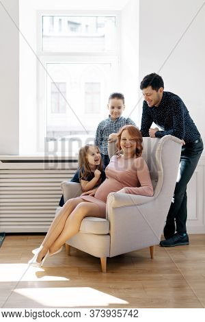 Happy Family Portrait At Home. Parents, Pregnant Mother And Father With Lovely Two Kids Sitting On T