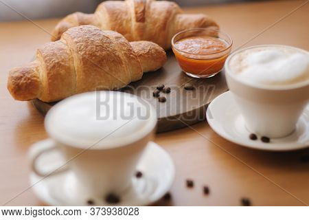 Morning Coffee And Croissant On Wooden Table. Cappuccino With Freshly Baked Criossant Ay Home. Empty