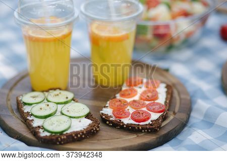 Picnic Basket With Healthy Vegan Sandwiches On Blue Checkered Blanket In Park. Fresh Fruits, Vegetab