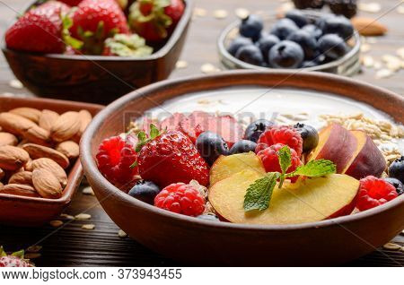 Fruit Healthy Muesli With Peaches Strawberry Almondsin Clay Dish With Yogurt On Wooden Kitchen Table