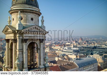 Aerial view of architectural construction of bell tower of St. Stephen's Basilica in Budapest, Hungary on a background of clear blue sky.