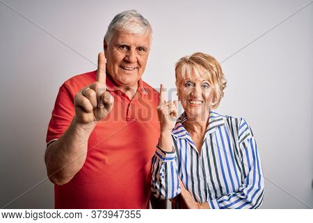 Senior beautiful couple standing together over isolated white background pointing finger up with successful idea. Exited and happy. Number one.